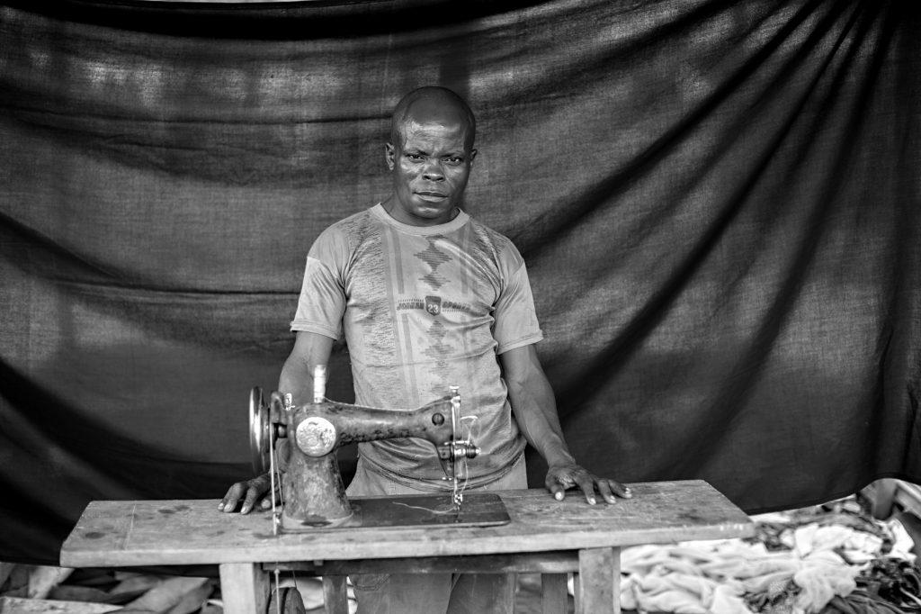 Benjamin, con su máquina de coser, de la que dice: «Es mi vida, es mi sangre. La utilizo para poder comprar comida para mi familia». Brian Sokol / ACNUR.